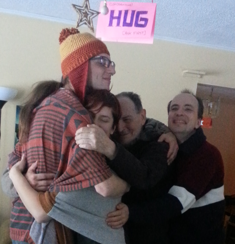 "Four people share a group hug under a sign that says, ""HUG."""