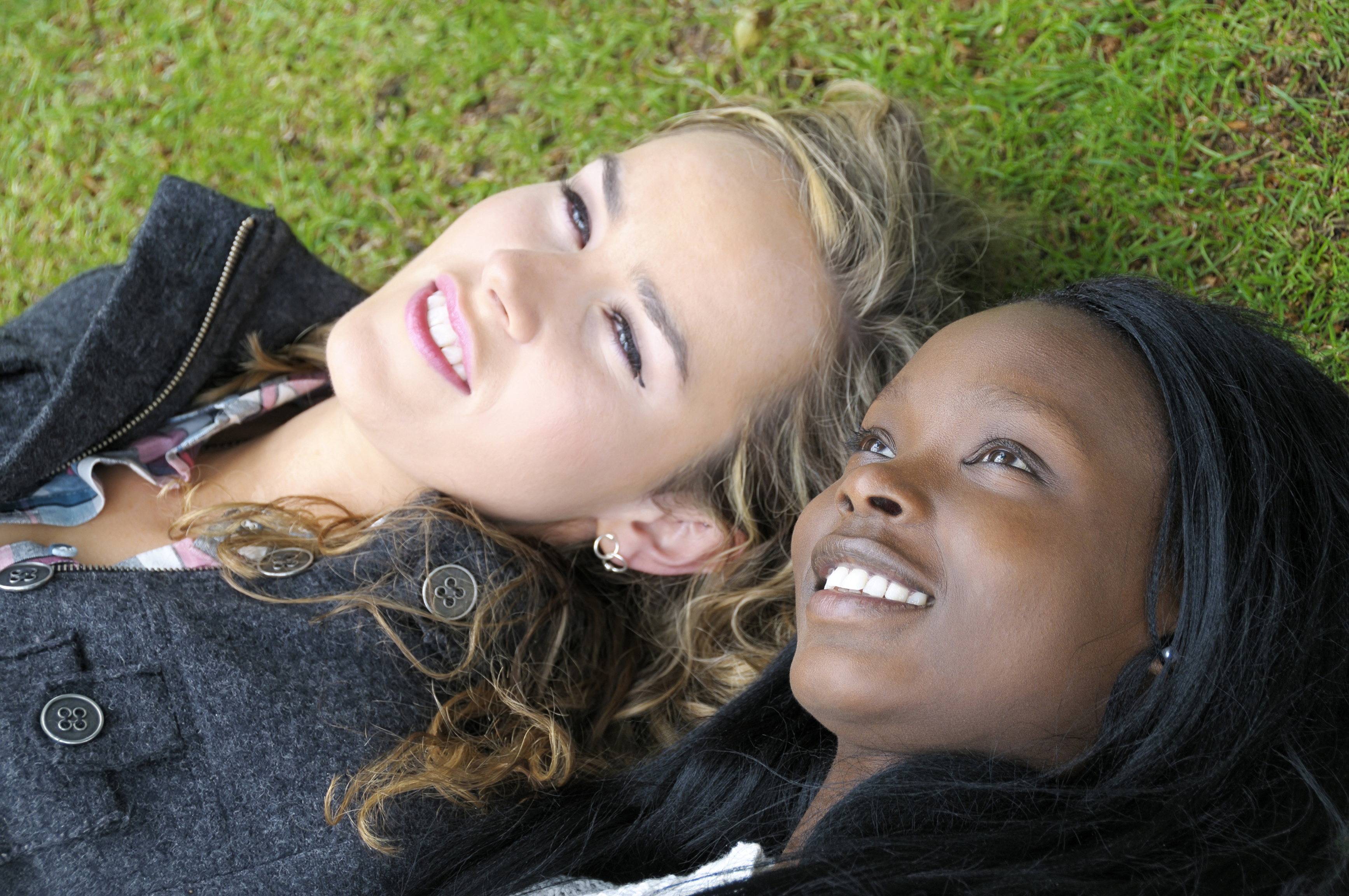 Two young women lying on the grass, beholding the beyond.